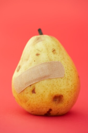 Bruised pear with band-aid