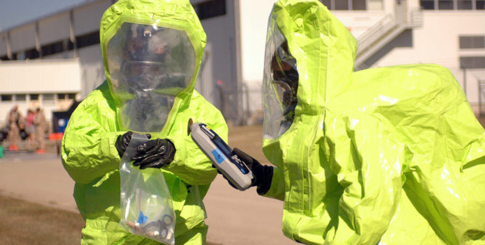 People in HAZMAT suits disposing of household chemicals