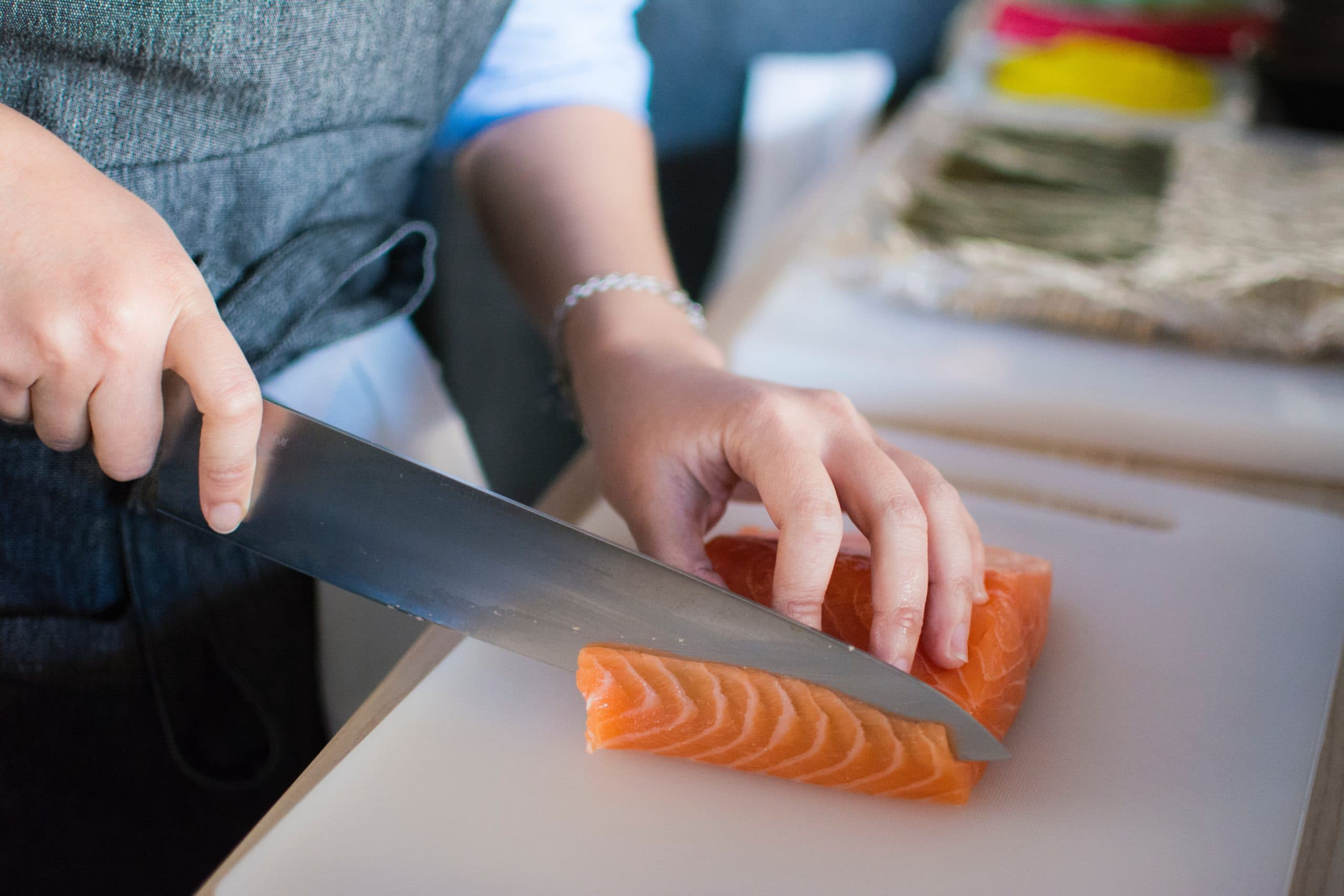 person slicing salmon on white cutting board