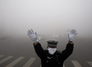 A policeman gestures as he works on a street in heavy smog in Harbin, northeast China's Heilongjiang province, on October 21, 2013. Choking clouds of pollution blanketed Harbin, which is famed for its annual ice festival, reports said, cutting visibility to 10 metres (33 feet) and underscoring the nation's environmental challenges. CHINA OUT AFP PHOTO (Photo credit should read STR/AFP/Getty Images)